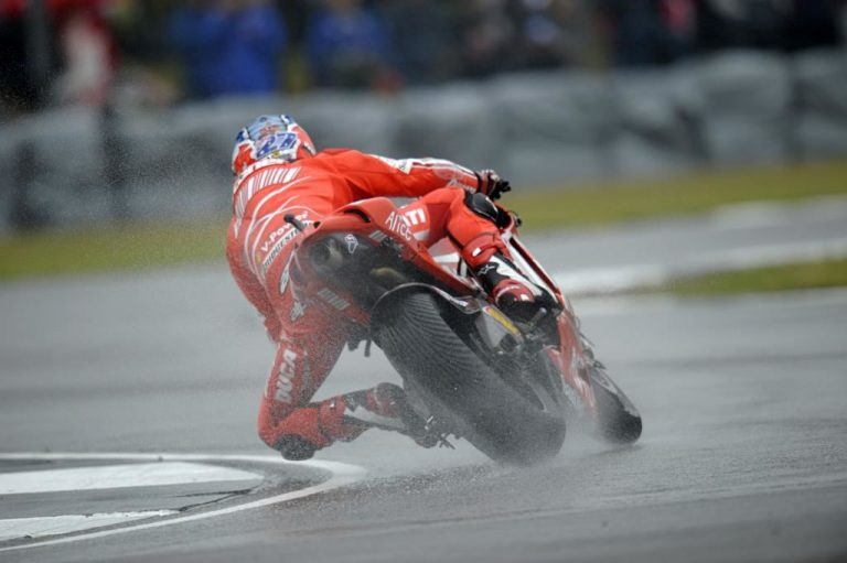 Stoner roars into pole position as news rocks Rossi