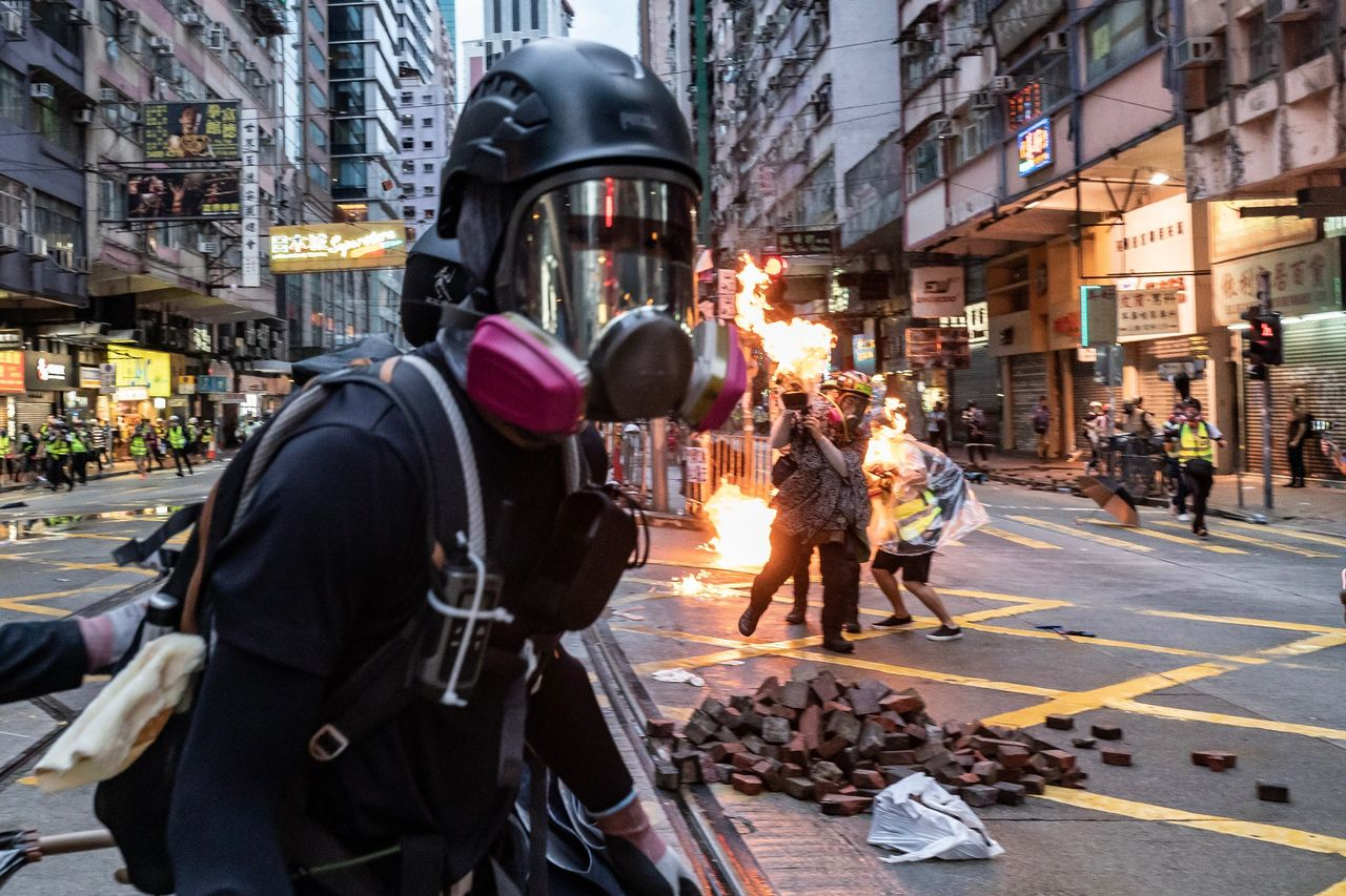 Tens of thousands of masked men march through Hong Kong in rejection of the emergency law