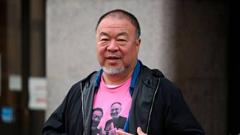 Chinese dissident Ai Weiwei plays a silent protest during the Assange trial